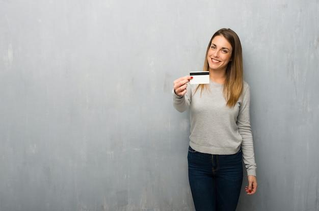 クレジットカードを保持している織り目加工の壁に若い女性