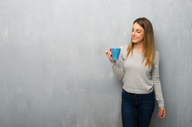 熱い一杯のコーヒーを保持している織り目加工の壁に若い女性