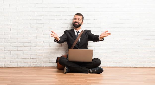提示し、手で来るように招待して床に座って彼のラップトップを持ったビジネスマン