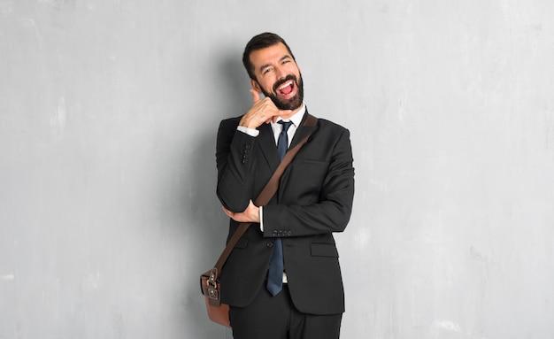 電話のジェスチャーを作るひげを持ったビジネスマン。私に折り返し電話する