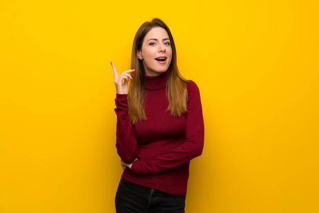 指を上向きのアイデアを考えて黄色の壁の上のタートルネックを持つ女性