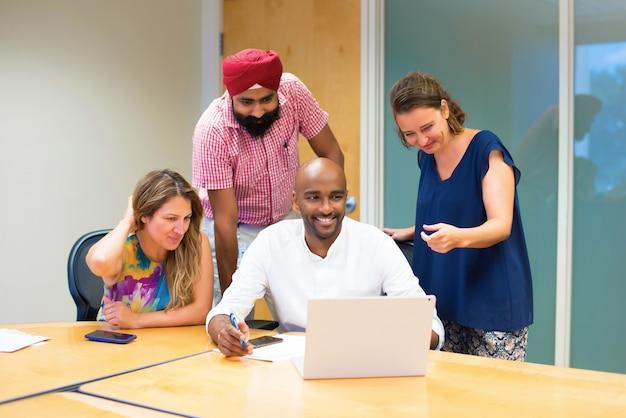 ラップトップを持つオフィスでさまざまな民族によって形成された歓喜チーム