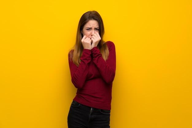 Женщина с водолазкой над желтой стеной нервно и страшно кладет руки в рот