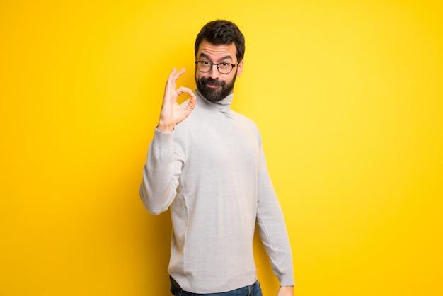 Человек с бородой и водолазкой, показывая знак ок с пальцами