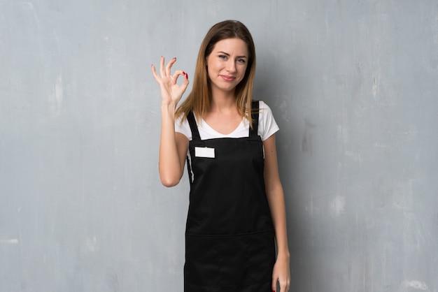 Сотрудник женщина показывает знак ок с пальцами