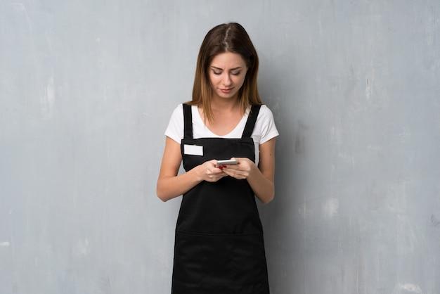 携帯電話でメッセージを送信する従業員の女性