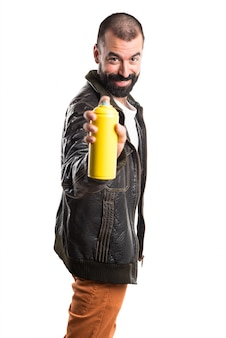 エアロゾルを持つ革ジャケットを着ている男