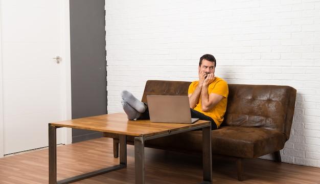 部屋で彼のラップトップを持つ男は少し緊張して口に手を入れて怖い