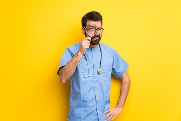 虫眼鏡を取るとそれを通して見る外科医医師男