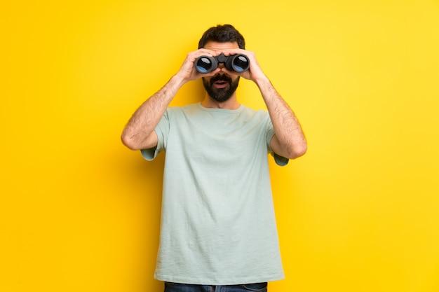 Человек с бородой и зеленой рубашкой и смотрит в бинокль вдаль