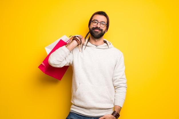 Хиппи человек с дредами держит много сумок