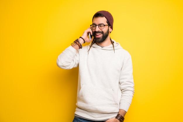 Хиппи человек с дредами ведет разговор по мобильному телефону