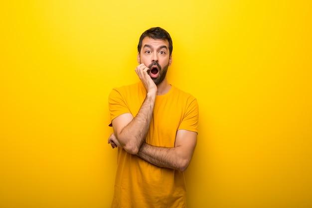 Человек на изолированном ярком желтом цвете удивленный и потрясенный пока смотрящ правый