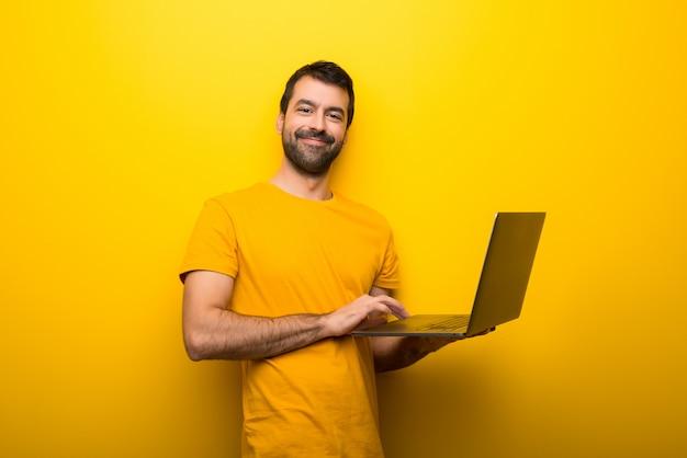 ノートパソコンと孤立した鮮やかな黄色の色の男