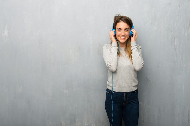 ヘッドフォンで音楽を聴く織り目加工の壁に若い女性