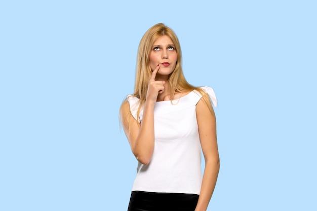 笑顔と分離の青い背景に自信を持って顔を正面に見ている若いブロンドの女性