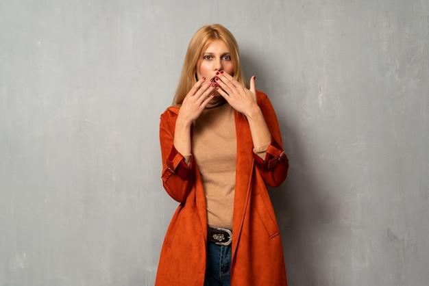 Женщина на текстурированном фоне немного нервничает и боится положить руки в рот