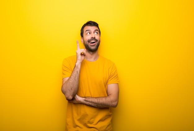 Человек на изолированном ярком желтом цвете думая идея указывая палец вверх