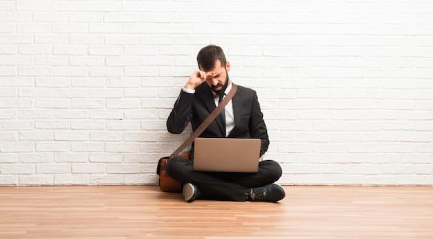 疲れて病気の表現で床に座って彼のラップトップを持ったビジネスマン