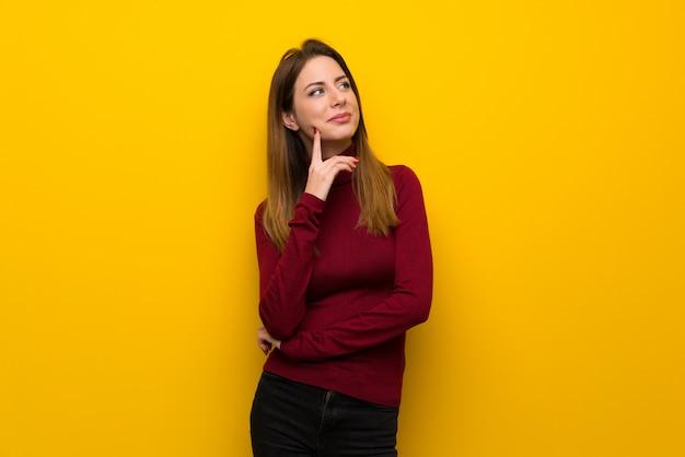 見上げながらアイデアを考えて黄色の壁の上のタートルネックを持つ女性
