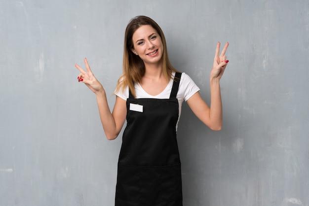 笑顔で両手で勝利のサインを示す従業員女性