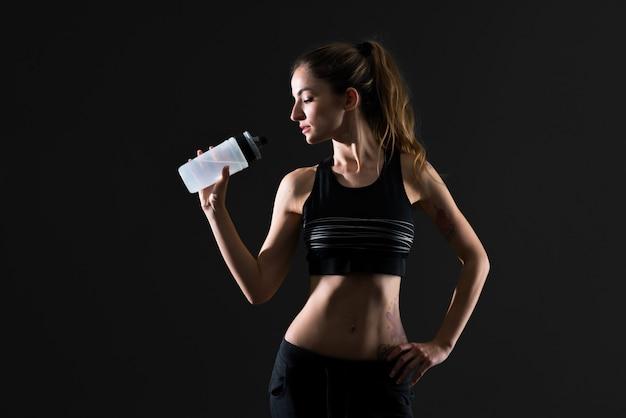 暗い背景に水のボトルを持つスポーツ女性