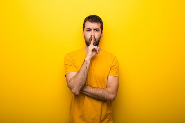 口の中に指を入れて沈黙ジェスチャーのサインを示す孤立した鮮やかな黄色の色の男