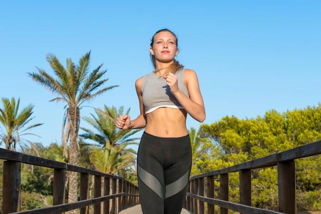 Молодая спортивная женщина делает упражнения и работает в парке