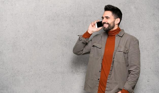 織り目加工の壁を越えて携帯電話との会話を続けるひげを持つハンサムな男