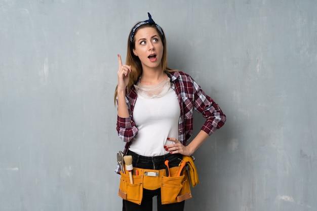 職人や電気技師の女性が指を上向きにする考えを考えて