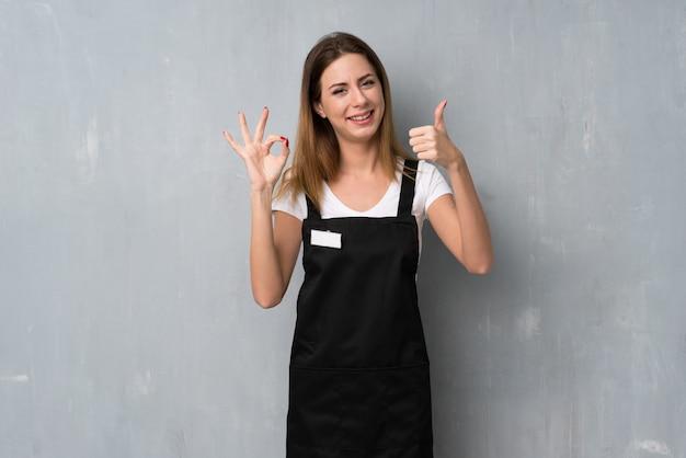 Женщина сотрудника показывает знак ок и показывает большой палец вверх