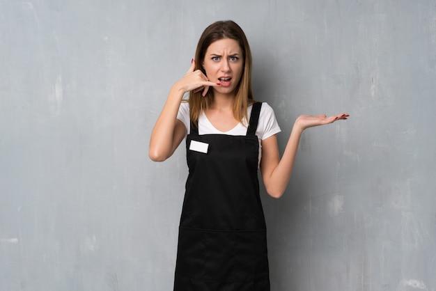 電話ジェスチャーを作ると疑う従業員女性