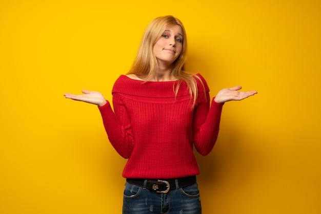 手と肩を上げながら疑問を持つ黄色の壁を越えて金髪の女性