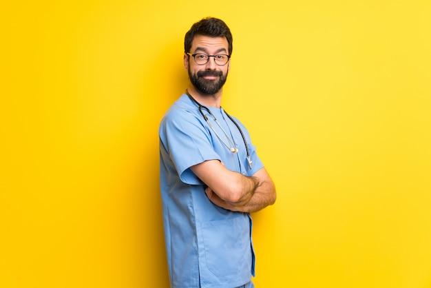 Хирург врач мужчина держит руки скрещенными в боковом положении во время улыбки