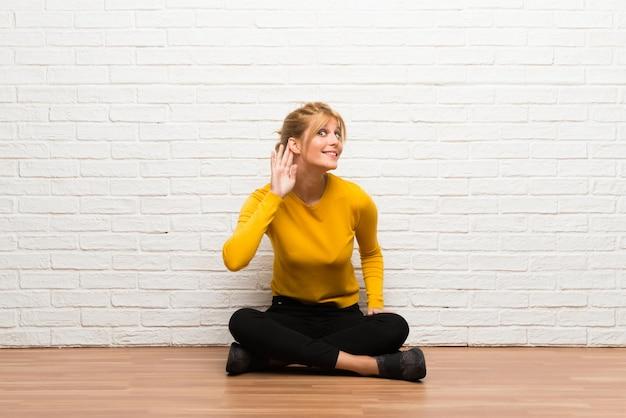 Молодая девушка сидит на полу, слушая что-то, положив руку на ухо