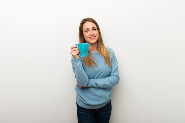 熱い一杯のコーヒーを保持している分離の白い背景の上の金髪の女性