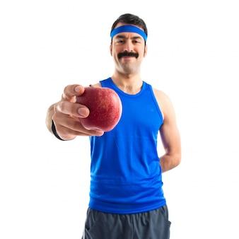 Спортмен держит яблоко