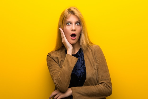Блондинка на ярком желтом фоне удивлена и шокирована, глядя прямо