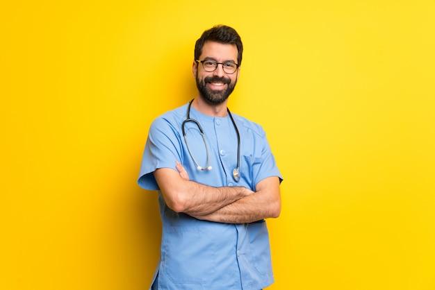 Хирург врач мужчина держит руки скрещенными в лобном положении