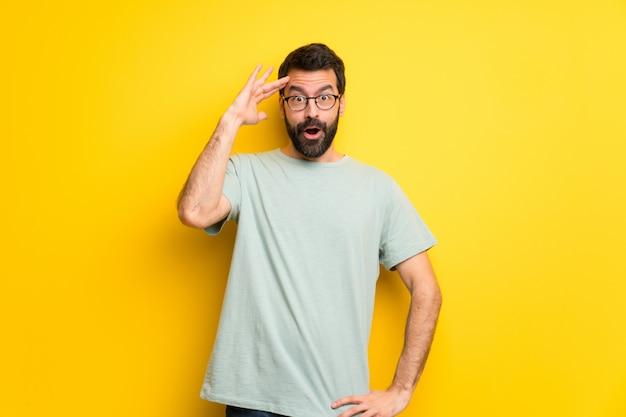 ひげと緑色のシャツを着た男は、何かを実感したばかりで、解決策を模索しています。