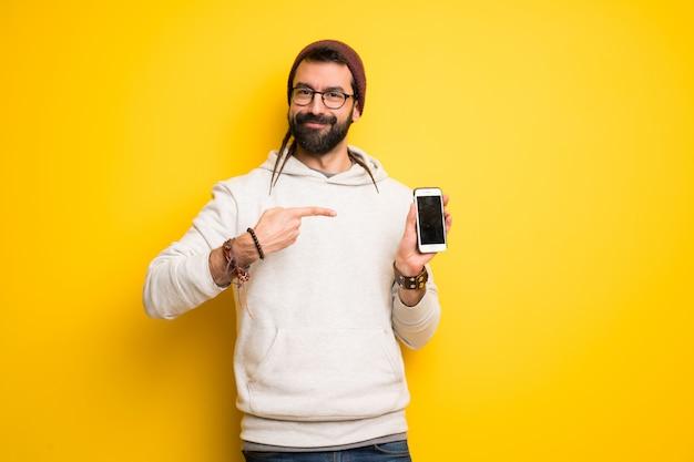 幸せと携帯を指しているドレッドヘアを持つヒッピー男