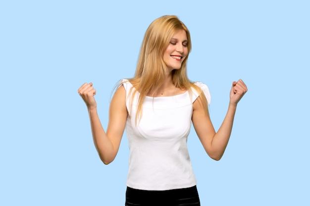 孤立した青い背景に勝利を祝う若いブロンドの女性