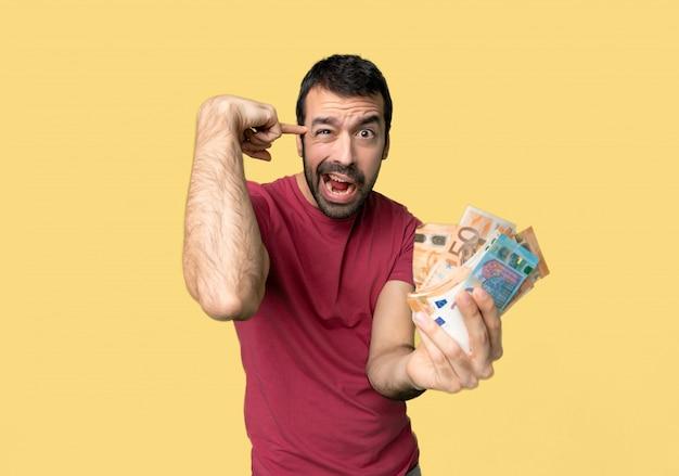 頭の上に指を置く狂気のジェスチャーを作るお金をたくさん取る人