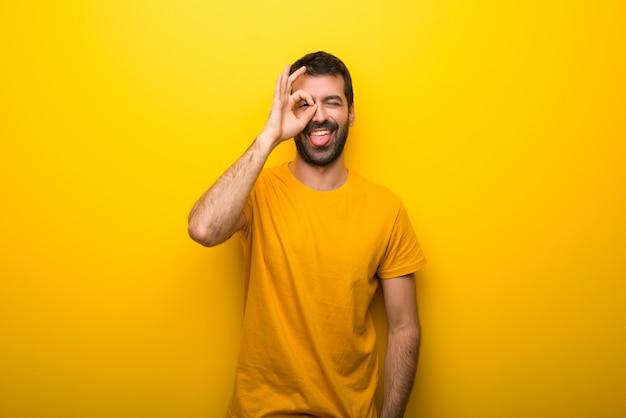 孤立した鮮やかな黄色の色の男は面白いとクレイジーな顔の感情になります