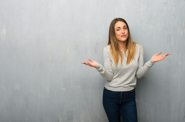 手と肩を上げながら疑問を持つ織り目加工の壁に若い女性