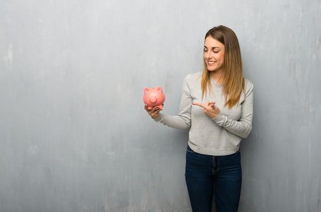 Молодая женщина на текстурированной стене держит копилку