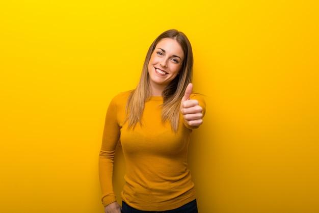 何か良いことが起こったのでジェスチャー親指をあきらめて黄色の背景に若い女性