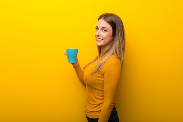 熱い一杯のコーヒーを保持している黄色の背景に若い女性
