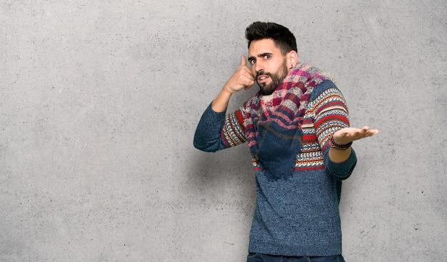 ヒッピー男電話ジェスチャーを作ると織り目加工の壁を疑う