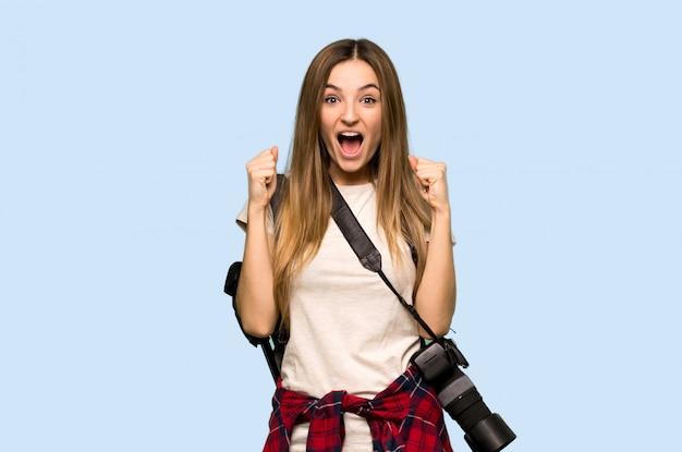 孤立した青い背景に勝者の位置で勝利を祝う若い写真家の女性